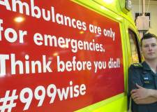 Dave Saxby, EMAS Clinical-Team Mentor, with the first advert to go on ambulances at the fleet workshop.