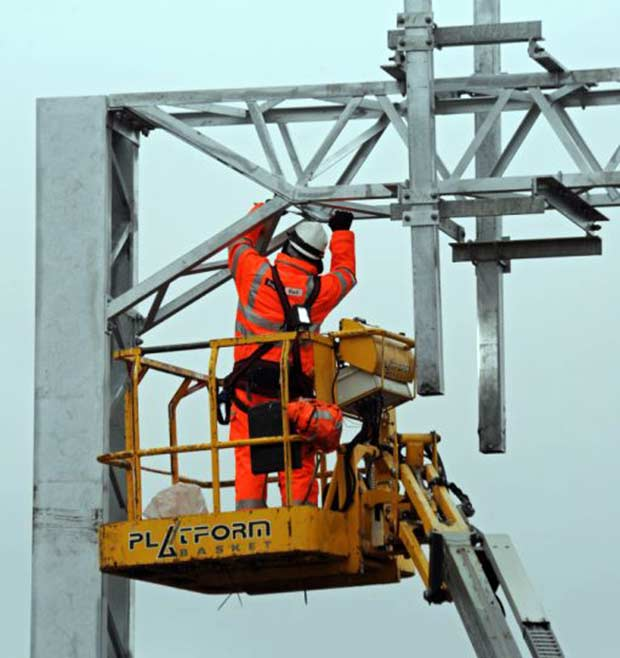An engineer works on overhead electric cabling for line electrification. Photo: Network Rail