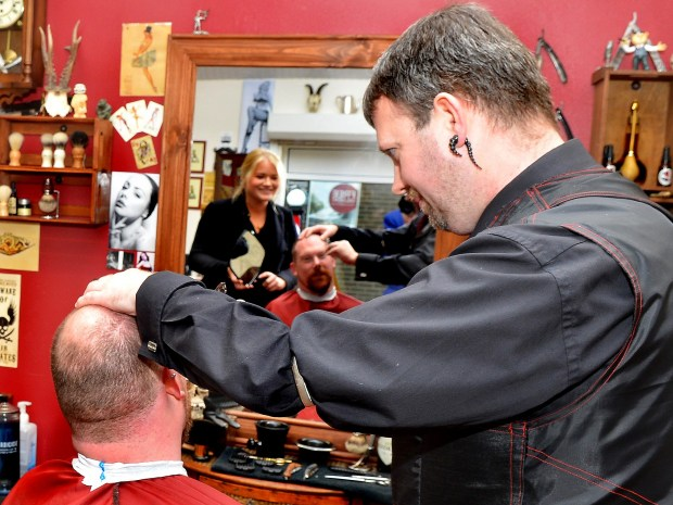 Barber Phil Walters with client Adrian Trevelyan and the reflection of Banks Long & Co surveyor Harriet Hatcher