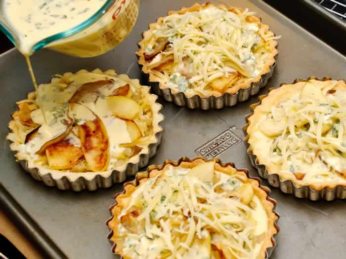 Pouring Custard on Savory Apple Tart with Onion, Cheddar & Blue Cheese