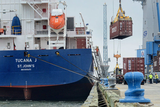 Cranes load containers onto a cargo ship docked at the Port of Gulfport. (file photo)