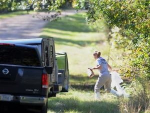 An investigator carries items from the wooded area along Shelby Road in rural Copiah County, Miss., on Tuesday, Nov. 5, 2013, where the bodies believed to be of a missing Jackson-area family where discovered in an abandoned house. Copiah County Sheriff Harold Jones says the bodies were found in an abandoned house about a mile from where the family's vehicle was located Saturday. (AP PHOTO/Joe Ellis, The Clarion-Ledger)