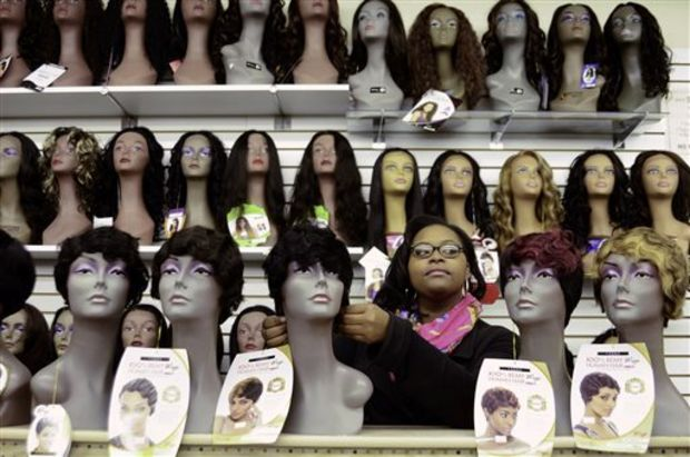 Sales person Jaleaza Tate straightens a wig at 2-U Beauty & Fashions, a beauty and cosmetics store in Columbus, Miss. Among Tate's responsibilities are maintaining the display wig heads and their styles. (AP Photo/The Commercial Dispatch, Luisa Porter)