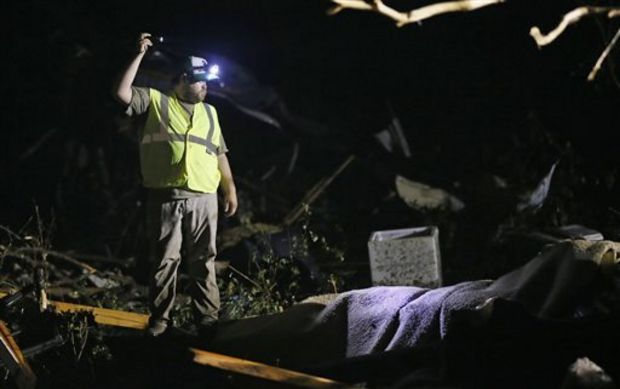 A responder shines his flashlight into the remains of several mobile homes as he searches for survivors in Louisville, Miss., early Tuesday morning, April 29, 2014 after a tornado hit the east Mississippi community Monday. (AP Photo/Rogelio V. Solis)