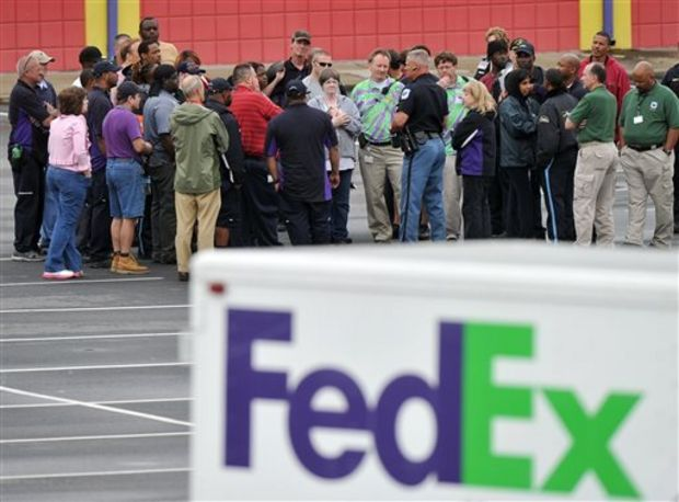 "A Cobb County Police Officer speaks to FedEx employees and family members gathered at the parking lot of a skating rink located near the shipping facility where a gunman open fire in Kennesaw, Ga., on Tuesday, April 29, 2014. A shooter described as being armed with an assault rifle and having bullets strapped across his chest ""like Rambo"" opened fire Tuesday morning at a FedEx station outside Atlanta, wounding at least six people before police found the suspect dead from an apparent self-inflicted gunshot. (AP Photo/Atlanta Journal-Constitution, Brant Sanderlin)"