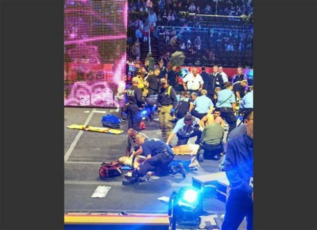 In this photo provided by Rosa Viveiros, first responders work at the center ring after a platform collapsed during an aerial hair-hanging stunt at the Ringling Brothers and Barnum and Bailey Circus, Sunday, May 4, 2014, in Providence, R.I. At least nine performers were seriously injured in the fall, including a dancer below, while an unknown number of others suffered minor injuries. (AP Photo/Rosa Viveiros) (Rosa Viveiros