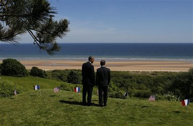 U.S. President Barack Obama and French President Francois Hollande look out at Omaha Beach, one of the sites of the Allied soldiers beach landings, at Normandy American Cemetery as they participate in the 70th anniversary of D-Day in Colleville sur Mer in Normandy, France, Friday, June 6, 2014. (AP Photo/Charles Dharapak)