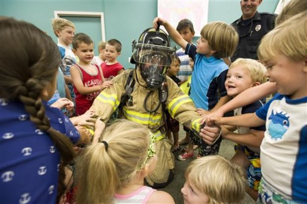 Firefighter Dustin McCullough demonstrates PPE (personal protective equipment) gear to children who participated in the summer library program at First Regional Library in Hernando, Miss. on Thursday, July 24, 2014. During the annual event, area firefighters teach children about fire safety and preparedness before leading them on a walk to the local fire department to cool off in the spray of a fire hose. (AP Photo/The Commercial Appeal, Brandon Dill)
