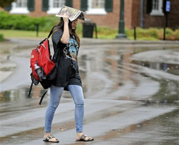 A University of Mississippi student uses a newspaper to shield her head from rain while walking across campus in Oxford, Miss., Monday, Oct. 13, 2014. Trees tumbled and some buildings were damaged Monday, but few injuries were reported as a strong cold front pushed a line of thunderstorms across Mississippi. (AP Photo/The Daily Mississippian, Thomas Graning