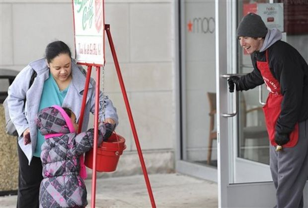 Windy DeLeon, 35, of Erie, Penn., helps her niece Kaylene DeLeon, 4, drop a donation in a Salvation Army kettle on Nov. 12 outside a Macy's department store near Erie, Pa. On Tuesday, a Salvation Army bell ringer was robbed outside a Winn Dixie in Gulfport. (Christopher Millette/The Associated Press)