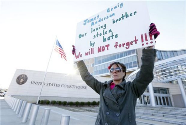 Amelie Hahn, braves cold weather as she holds a poster memorializing the 2011 rundown death of James Craig Anderson in front of the federal courthouse in Jackson, Miss., Wednesday, Jan. 7, 2015. Two of the men charged in the series of 2011 racial beatings that resulted in Anderson's death were expected at a change-of-plea hearing. (AP Photo/Rogelio V. Solis)