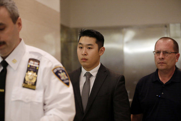 New York City rookie police officer Peter Liang, center, leaves the courtroom after his arraignment at Brooklyn Superior court, Wednesday, Feb. 11, 2015, in New York. Liang, who fired into a darkened stairwell last November at a Brooklyn public housing complex, accidentally killing 28-year-old Akai Gurley, was indicted by a grand jury in the shooting. (AP Photo/Mary Altaffer)