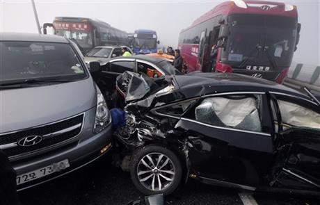 Damaged vehicles sit on Yeongjong Bridge in Incheon, South Korea, Wednesday, Feb. 11, 2015. Two people were killed and at least 42 were injured on Wednesday after a pileup involving about 100 vehicles in foggy weather on the bridge near the Incheon International Airport, South Korean officials said. (AP Photo/Yonhap, Suh Myung-gon)
