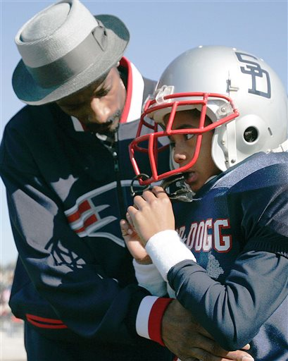 In this Feb. 5, 2005 file photo, Rap artist and actor Snoop Dogg, left, talks to his son Cordell Broadus, 7, a member of the the Snoop All-Stars youth football team, before their game against the Jacksonville All-Stars in Snoop Bowl at Raines High School in Jacksonville, Fla. Broadus, a wide receiver from Bishop Gorman High School in Las Vegas, spurned Snoop Dogg's favorite college team USC and signed with the UCLA Bruins Wednesday Feb. 4, 2015. (AP Photo/Robert E. Klein, File)