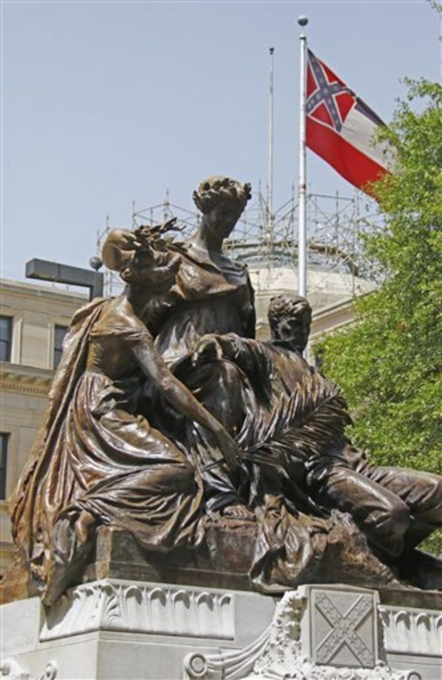 A statue erected in memory of the mothers sisters, wives and daughters of the Confederate soldiers sits before the state Capitol in Jackson, Miss., Tuesday, June 23, 2015, as the state flag flies behind it. Republican Lt. Gov. Tate Reeves said Tuesday, that Mississippi voters, not lawmakers, should decide whether to remove the Confederate battle emblem from the state flag. Reeves, who presides over the state Senate, spoke about the issue a day after Republican House Speaker Philip Gunn called the emblem offensive and said the state flag should change. (AP Photo/Rogelio V. Solis)