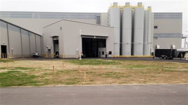 In this Friday, Oct. 2, 2015, photo, silos for holding carbon black, an ingredient that's mixed with rubber, oil and other ingredients to make tires, stand next to the receiving area of the $300 million Yokohama tire plant in West Point, Miss. Mississippi and local governments spent $82 million to incentivize Yokohama's first phase, scheduled to hire 500 workers. (AP Photo/Jeff Amy)