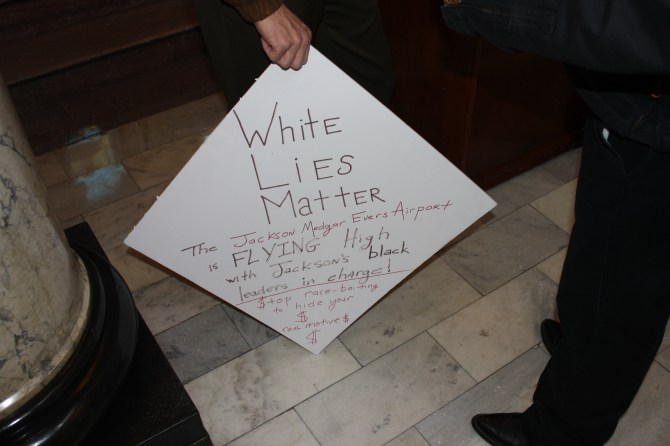 An Coalition for Economic Justice supporter's sign was on display at the press conference. PHOTO BY SHANDERIA K. POSEY