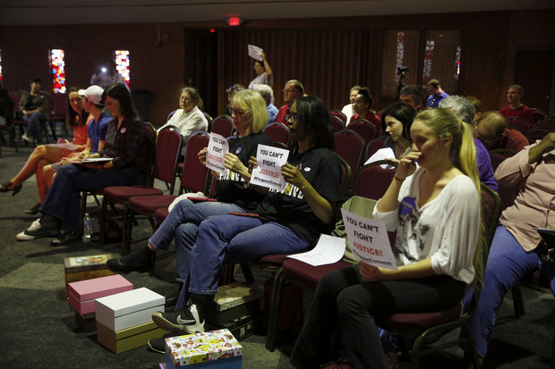 In this March 15, 2016 file photo, people watch and hold signs as members of the Ferguson City Council meet in Ferguson, Mo. St. Louis-area residents were sounding off Tuesday, April 19, 2016 in the last public hearing on the U.S. Department of Justice's settlement that calls for sweeping changes in Ferguson, where 18-year-old Michael Brown was fatally shot by a police officer. (AP Photo/Jeff Roberson, File)