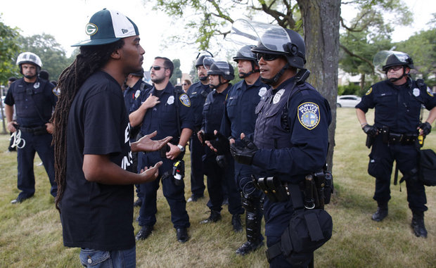 "A man speaks with police in a park in Milwaukee following a night of violence that left half a dozen businesses in flames, the Milwaukee police chief expressed surprise at the level of unrest that erupted after the fatal shooting of a black man Saturday by a black officer. ""This was, quite frankly, unanticipated,"" Chief Edward Flynn said Monday, two days after the worst of the rioting hit the Sherman Park neighborhood on the city's economically depressed and largely black north side. (Jeffrey Phelps / AP)"