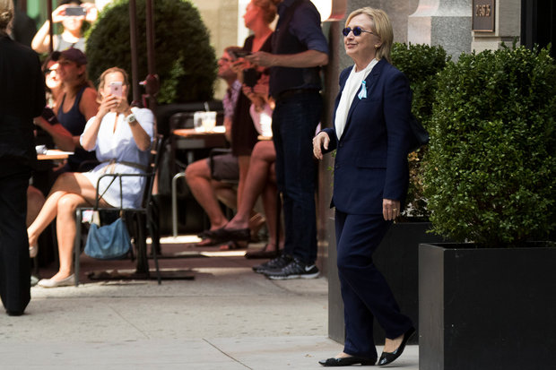 "Democratic presidential candidate Hillary Clinton leaves an apartment building Sunday, Sept. 11, 2016, in New York. Clinton's campaign said the Democratic presidential nominee left the 9/11 anniversary ceremony in New York early after feeling ""overheated."" (AP Photo/Andrew Harnik)"