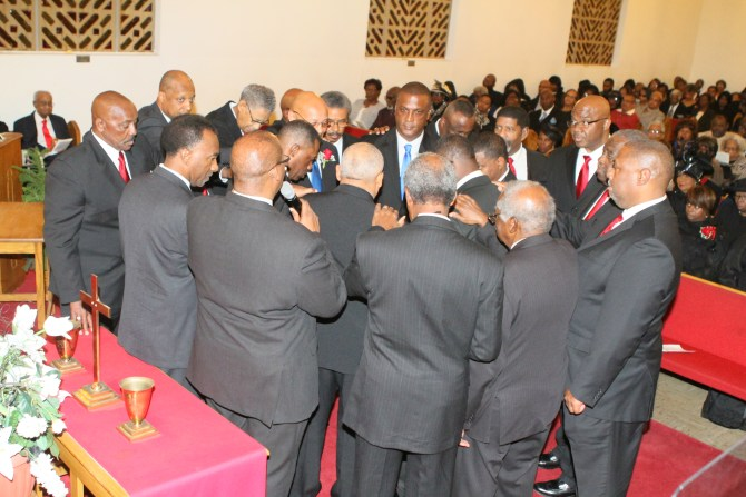 Current deacons and ministers laying hands on new deacons during ordination charge