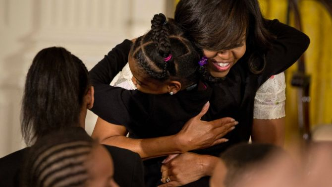 This April 20, 2016 file photo shows First Lady Michelle Obama giving a hug to a child during the annual White House Take Our Daughters and Sons to Work Day event attended by the children of Executive Office employees, young people from Big Brothers Big Sisters of America, SchoolTalk, and the D.C. Child and Family Services Agency, in the East Room of the White House in Washington. The feel-good initiatives of First Lady Michelle Obama have served as both inspiration and eight years of teaching moments for many families. AP Photo/Jacquelyn Martin