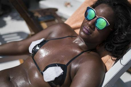 In this Jan. 11, 2017 photo, a woman in search of crisp tan lines lounges in the sun wearing a bikini made of black electrical tape at the Erika Bronze rooftop salon in the suburb of Realengo in Rio de Janeiro, Brazil. Dermatologists are more horrified than impressed with the technique, which they say can increase the chance of getting skin cancers, including melanoma. (AP Photo/Renata Brito)