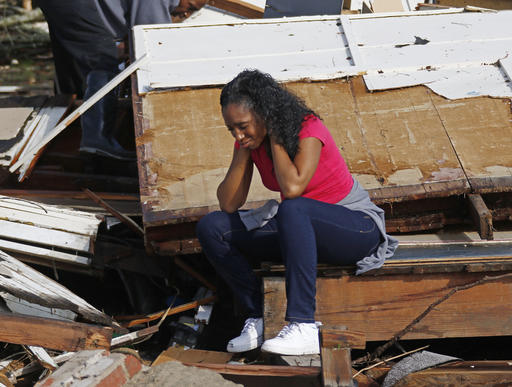 Shanise McMorris grieves on the slab of her Hattiesburg, Miss., home after an early tornado hit the city, Saturday, Jan. 21, 2017.  The tornado was part of a wall of stormy weather traveling across the region, bringing with it rain and unstable conditions.  (AP Photo/Rogelio V. Solis)