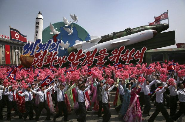 "In this Saturday, April 15, 2017, photo, North Korean men and women wave flags and plastic flowers as a float with model missiles and rockets with words that read ""For Peace and Stability in the World"" is paraded across Kim Il Sung Square during a military parade in Pyongyang. (AP Photo/Wong Maye-E)"