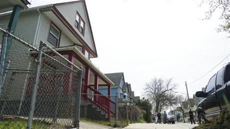 Steve Stephens' childhood home, left, is shown as neighbors chat down the street in Cleveland, Ohio, Monday, April 17, 2017. Authorities in Cleveland have expanded their manhunt nationwide for Stephens, a man suspected of gunning down a retiree and posting a video of the crime on Facebook. (AP Photo/Dake Kang)
