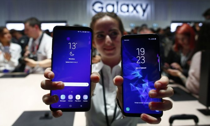 A woman holds the new Galaxy S9 and S9 Plus.