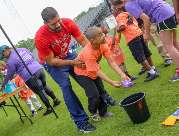 George Stewart helps his son Landon, a Gary Road Elementary student, with a game at special education field day on May 2 at Hinds Community College. (April Garon/Hinds Community College)