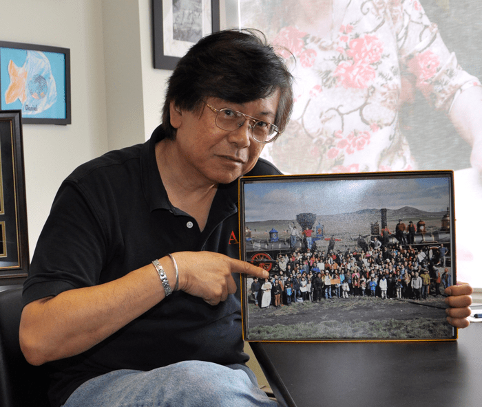 "Corky Lee at 2015 interview for ""The Force of Ethics in Civil Rights"" Oral History Project, points to his 2014 groundbreaking reenactment image with Chinese descendants: ""Photographic Justice."" Photo credit: David M. Bernstein"