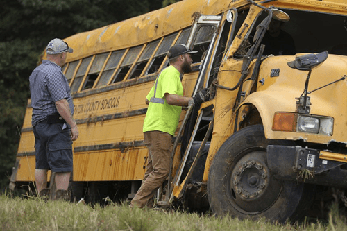 Wrecker crews inspect the damage to a Benton County School bus that was involved in wreck along U.S. Highway 72 near Walnut, Miss., Tuesday, Sept. 10, 2019, that resulted in the death of the driver and sent several students to the hospital. Thomas Wells/The Northeast Mississippi Daily Journal via AP