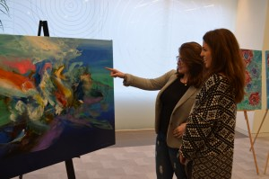 Viewers Look at a Hebert Sanchez Painting at the Aquamarine Exhibition