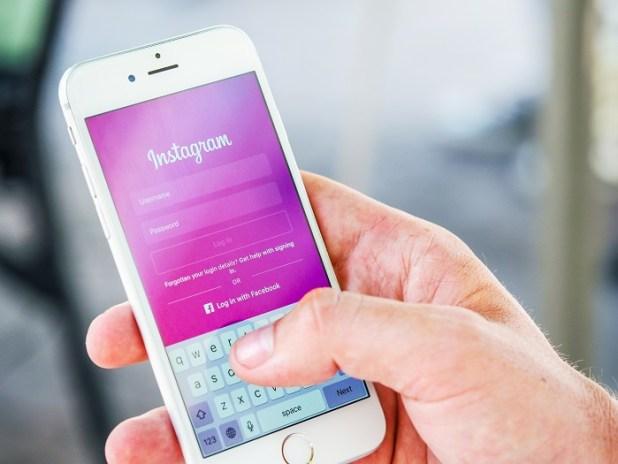 Instagram app showed n an iPhone display, held by a man