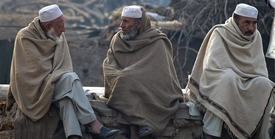 Afghan refugees who fled their country due to war and famine, sit at a roadside during the winter in Islamabad, Pakistan on Tuesday, Jan 31, 2012. (AP Photo/B.K.Bangash)