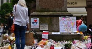 A woman looks at flowers in Albert Square in Manchester, northwest England on May 24, 2017, placed in tribute to the victims of the May 22 terror attack.