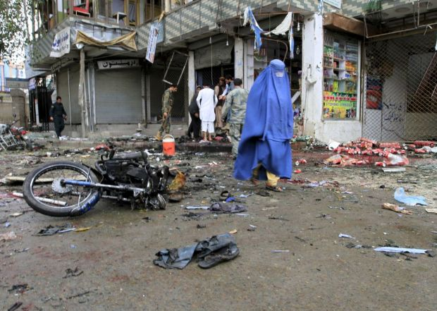 An Afghan woman walks through the cite of a suicide attack in Jalalabad, the capital city of eastern Afghan province, Nangarhar. Photo: Reuters