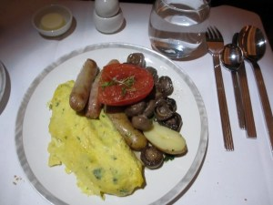 Breakfast option 2: an omelet with Brie, chives and spinach, and sides of chicken sausage, potatoes and glazed mushrooms.