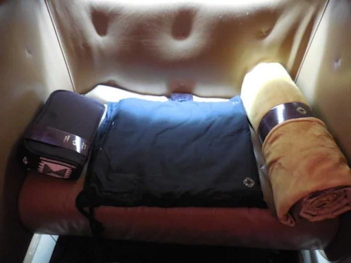 Ottoman holding amenity kit, blanket and pajamas.