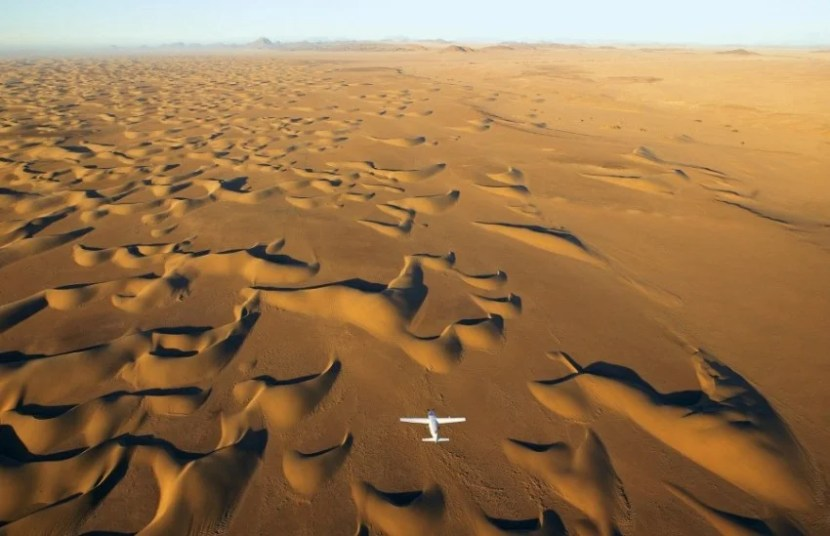 A plane flies over the expansive Namib Desert in Africa. Photo courtesy of Boundless Journeys.