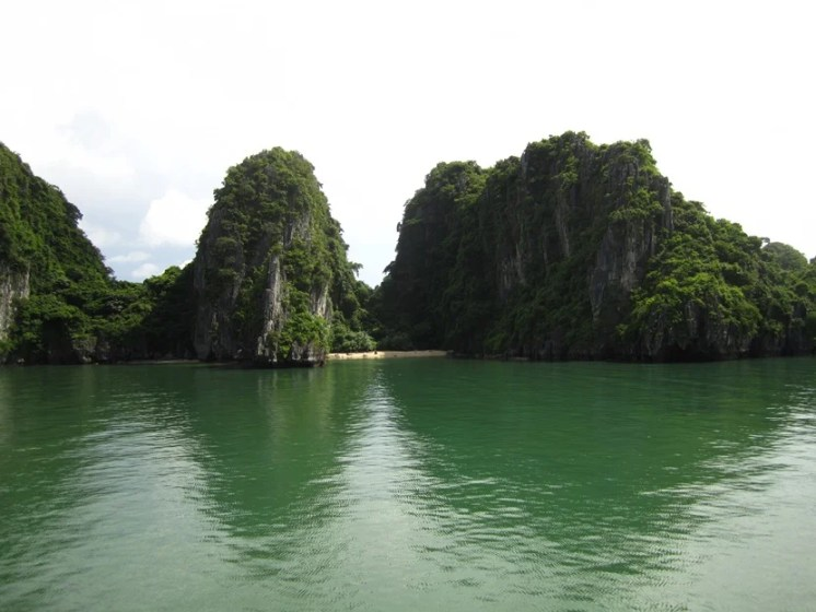 Limestone pillars and a secluded beach in Halong Bay