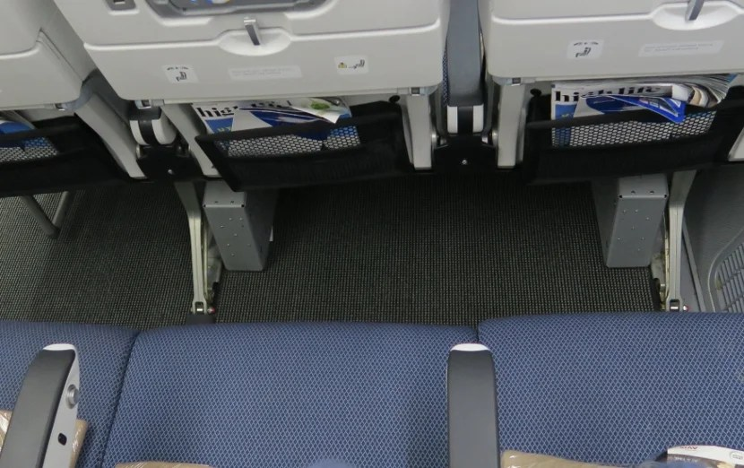 Overhead view of the entertainment boxes the restrict leg room for seats H, J, and K on the right side of the World Traveller section.