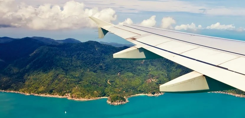 Airplane wing tip over ocean and island featured shutterstock 137460476