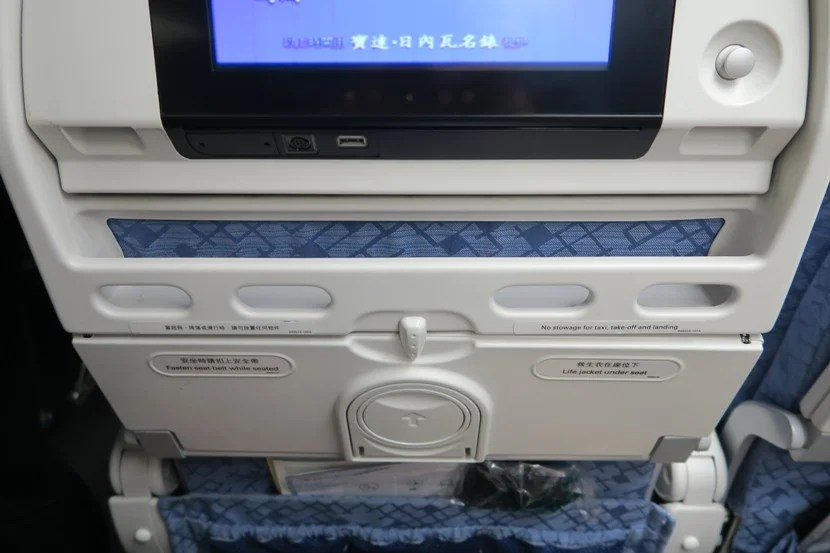 The tray below the IFE screen is very useful for storing your cell phone and boarding pass.