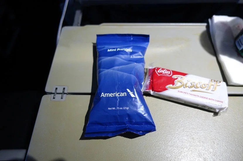 American Airlines offers two complementary snacks: Pretzels, and Biscoff biscotti's (although the flight crew doesn't like to give both).