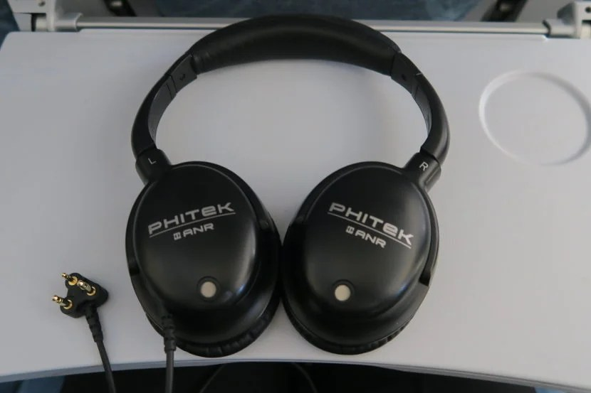 The noise canceling headphones provided to the Economy Comfort passengers were comfortable and effective.