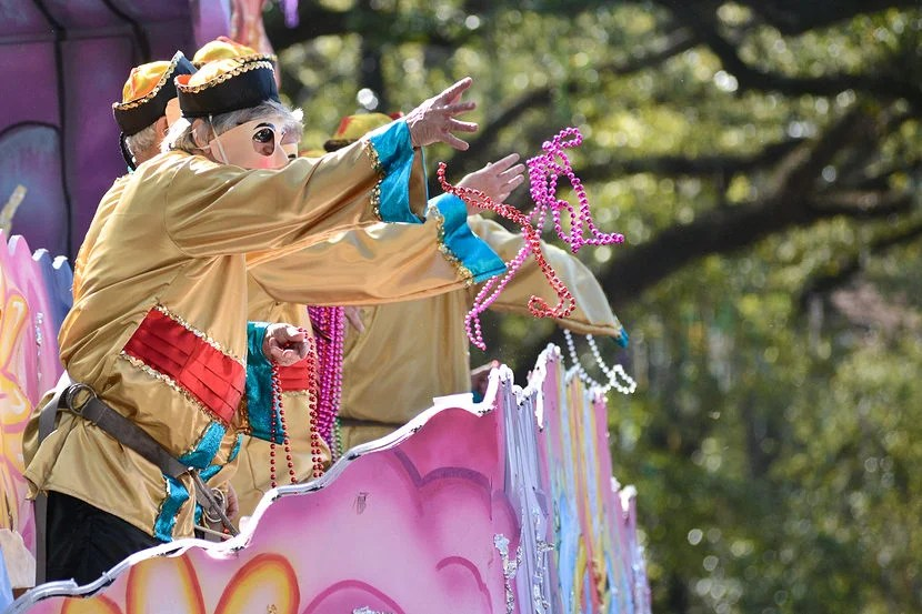 """Catching """"throws"""" during parades is a must-do activity for both adults and kids during Mardi Gras. Image courtesy of Shutterstock."""
