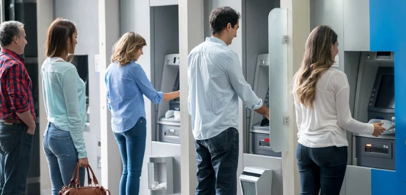 Group of people in a line at an ATM waiting to make a cash withdrawal. Image courtesy of Getty Images.